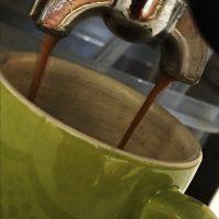 Espresso läuft aus der Siebträgermaschine in eine grüne Tasse