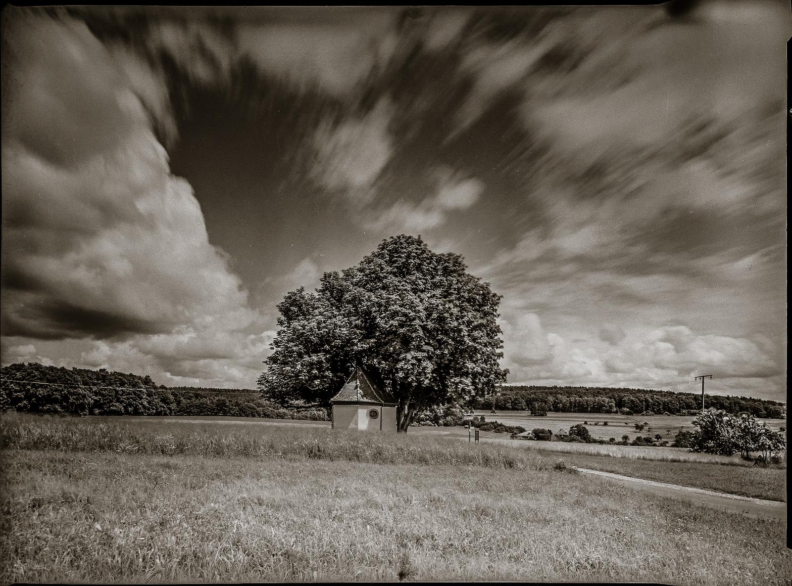 Kapelle unter Bäumen, starker Weitwinkel