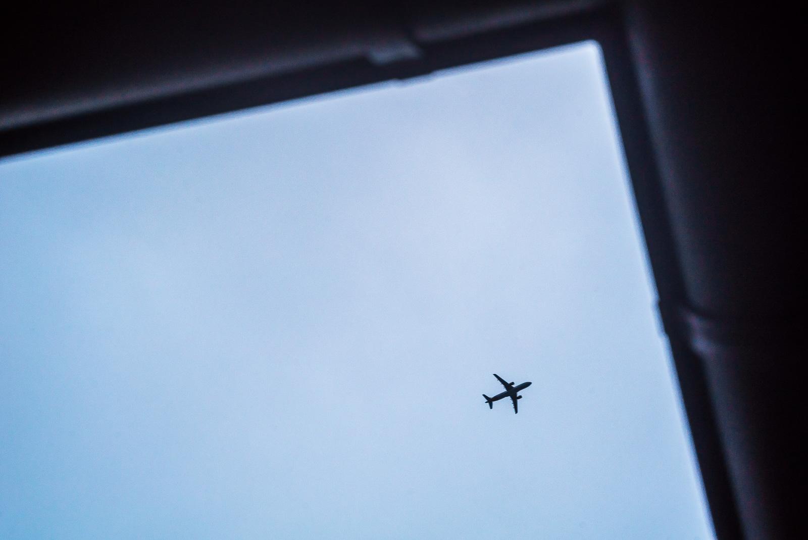 fliegendes Flugzeug von unten, von Dachrinne eingerahmt