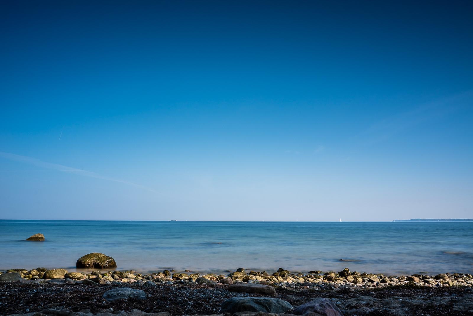 Ostseeküste vor Travemünde / Brodten, 2:1-Aufteilung mit klarem blauem Himmel über blauem Wasser