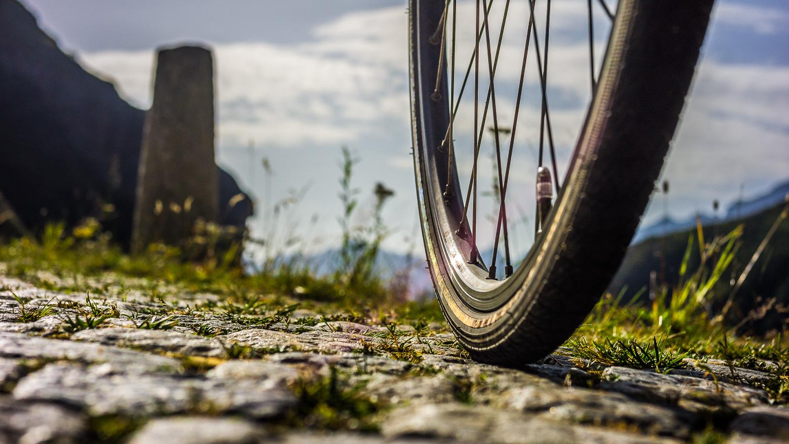 Rennradreifen auf Kopfsteinpflasterstraße vor Bergkulisse